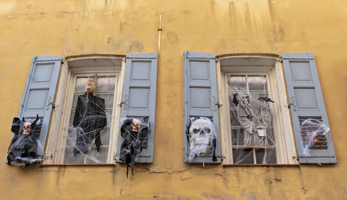 You can use stuff you can find at the nearest Halloween store, such as zombies and skeletons to decorate your windows!